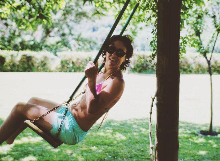 Portrait of woman enjoying on swing in park