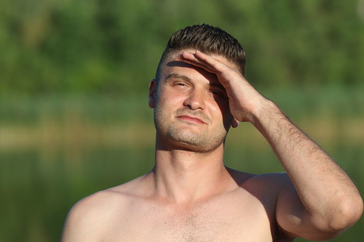 Close-up portrait of shirtless man shielding eyes in forest