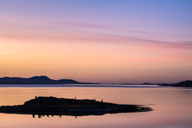 Silhouette of peninsula with reflections in smooth fjord during sunset Beauty In Nature Dusk Fjord Getting Away From It All Idyllic Island Mountain Mountain Range Nature No People Orange Color Outdoors Peninsula Pink Color Reflection Remote Sea Silhouette Sky Smooth Sunset Tranquil Scene Tree Water Waterfront