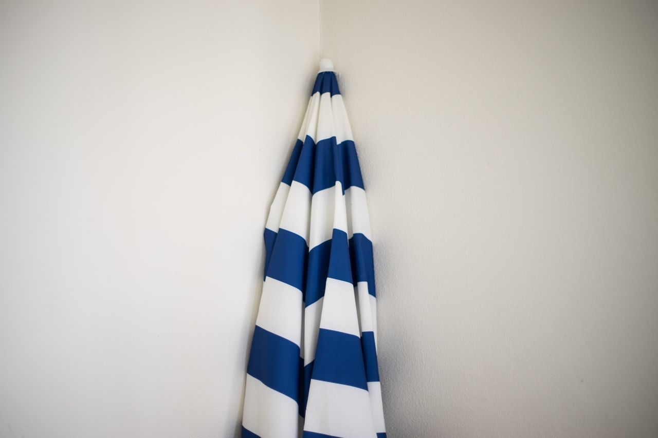 Striped sunshade leaning against white wall