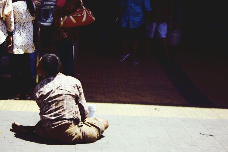Beggar sitting on road in city