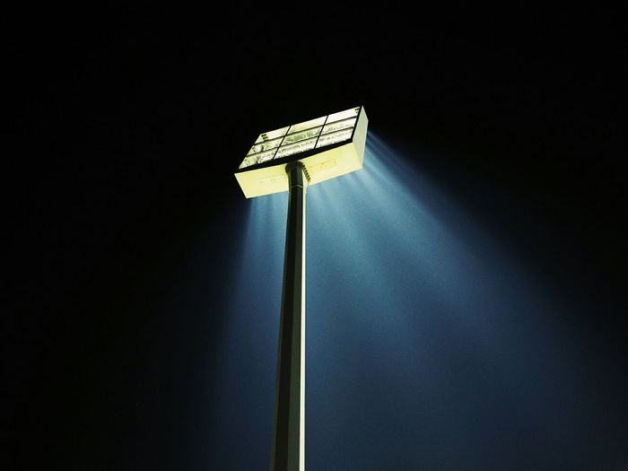 Low angle view of illuminated floodlight against sky