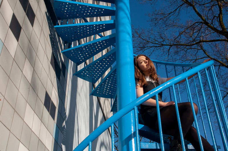 Low angle view of woman looking at railing
