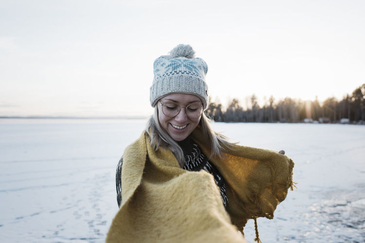 Portrait of smiling woman in snow against sky