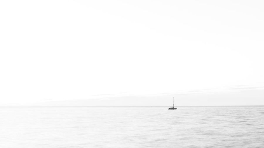 Sailboat in sea against clear sky