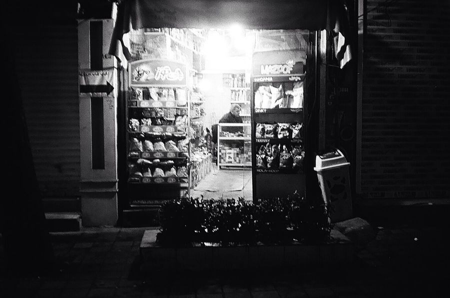 Grocery Shop In The Shop  One Man Only One Person Focus On Background Illuminated Night 35mm Film Street Photography Streetphoto_bw Black And White