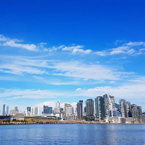 Sea By Cityscape Against Blue Sky