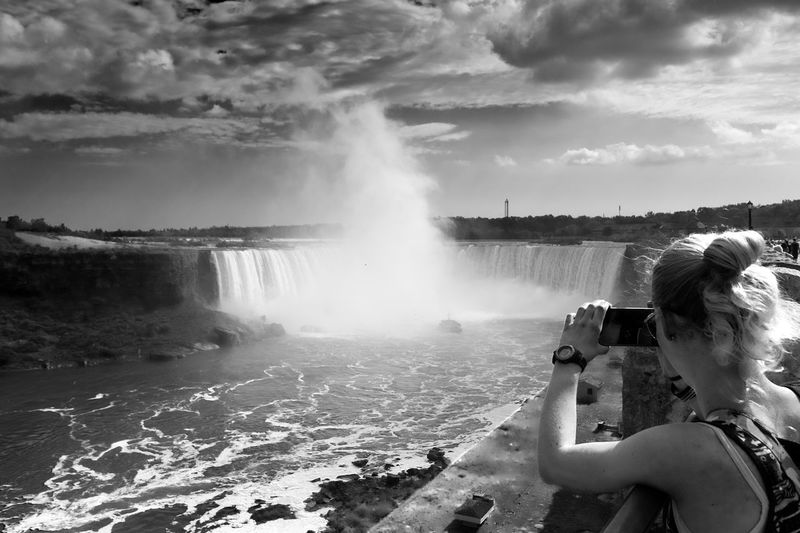Rear View Of Woman Photographing Niagara Falls Against Sky