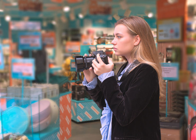 Side view of young woman photographing