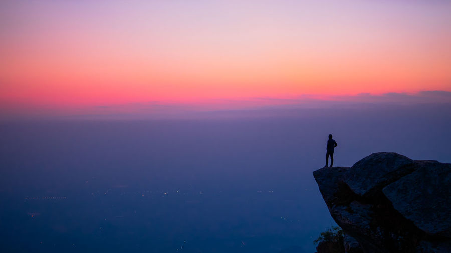 Silhouette man standing on cliff against sky during sunset