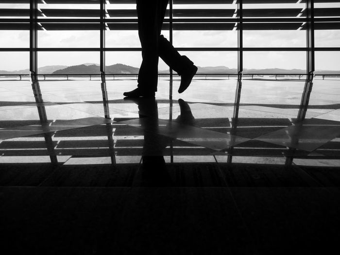 Low Section Of Silhouette Man Walking On Shiny Floor