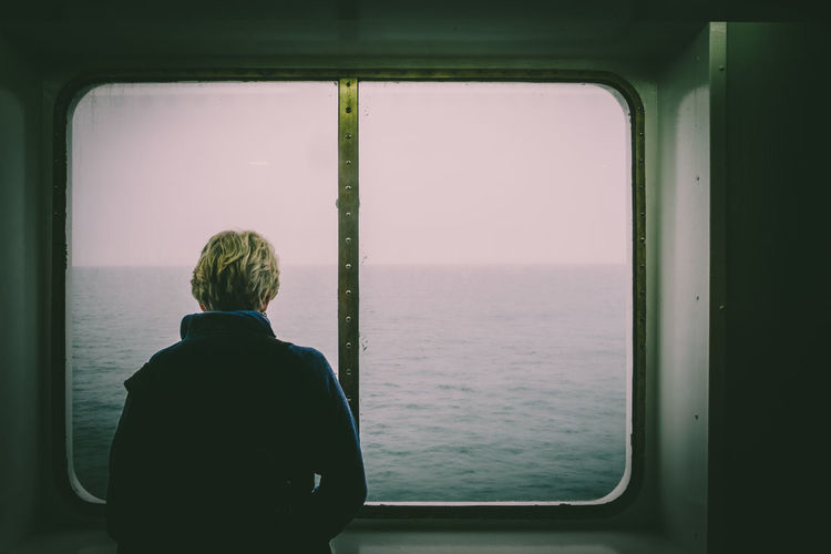 Rear view of man looking through window from ship