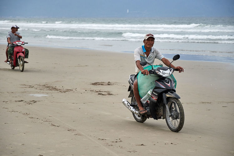 Vietnam Beach Danangbeach Day Full Length Headwear Helmet Land Vehicle Leisure Activity Lifestyles Men Motorcycle Nature Outdoors People Real People Riding Sand Sea Sky Transportation Vacations Water Young Adult