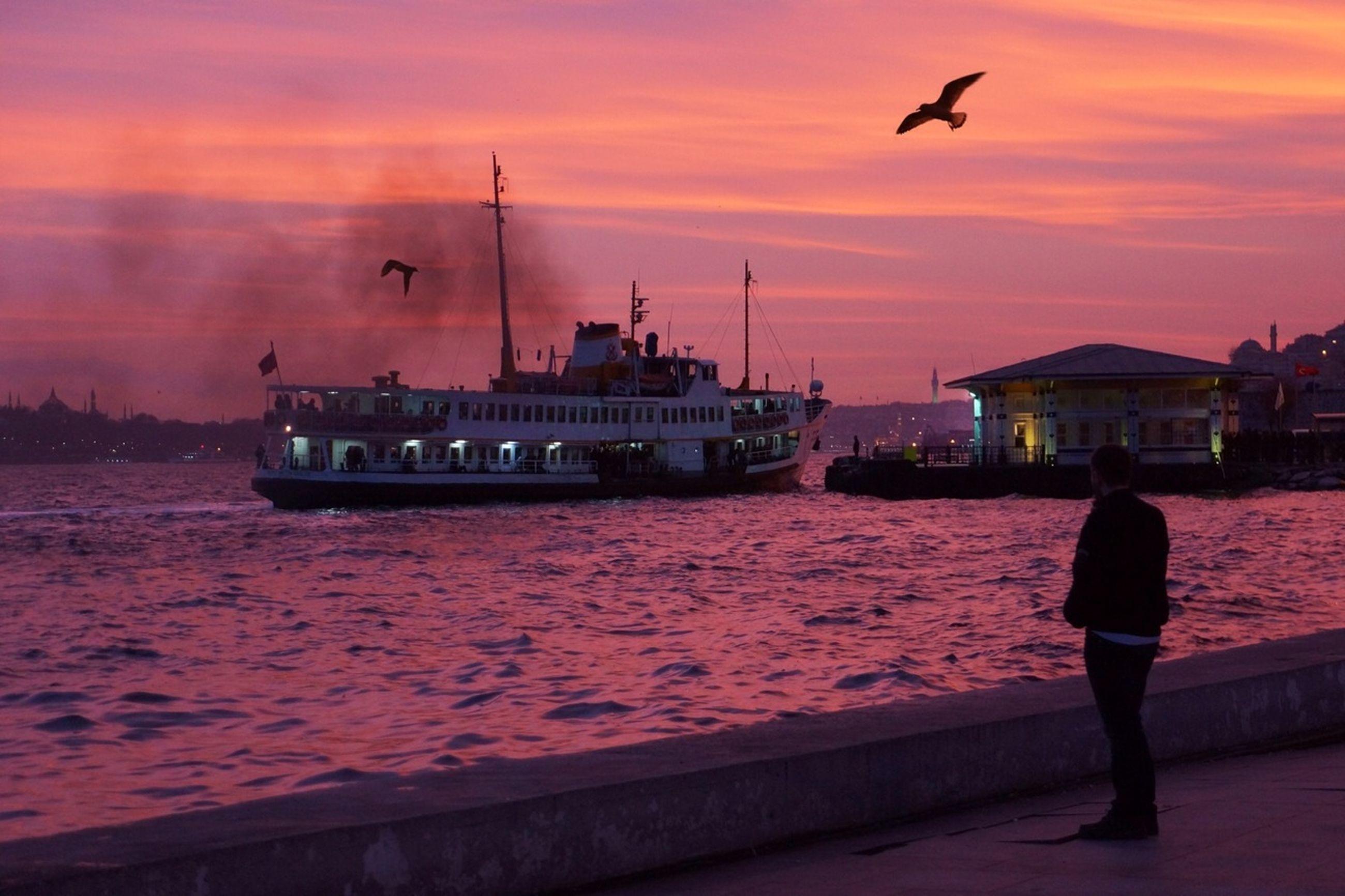 sunset, water, sky, built structure, orange color, sea, architecture, building exterior, bird, lifestyles, flying, leisure activity, men, silhouette, cloud - sky, pier, rear view, person