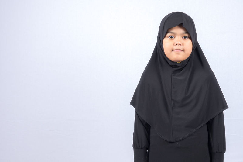 Portrait of young kid muslimah wearing hijab. Child Childhood Clothing Copy Space Front View Headscarf Hijab Indoors  Looking One Person Portrait Religion Standing Studio Shot Traditional Clothing Veil White Background