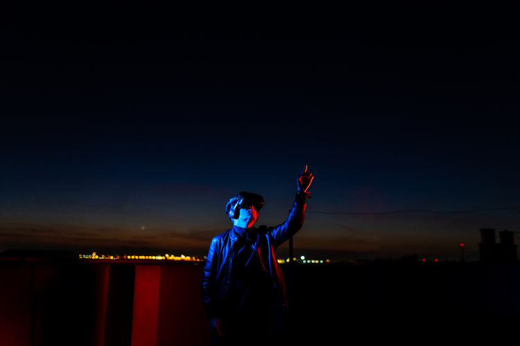 Full length of man standing against illuminated sky at night