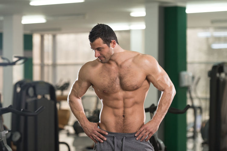 Muscular young athlete standing in gym