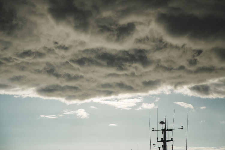 Low angle view of electricity pylon against storm clouds