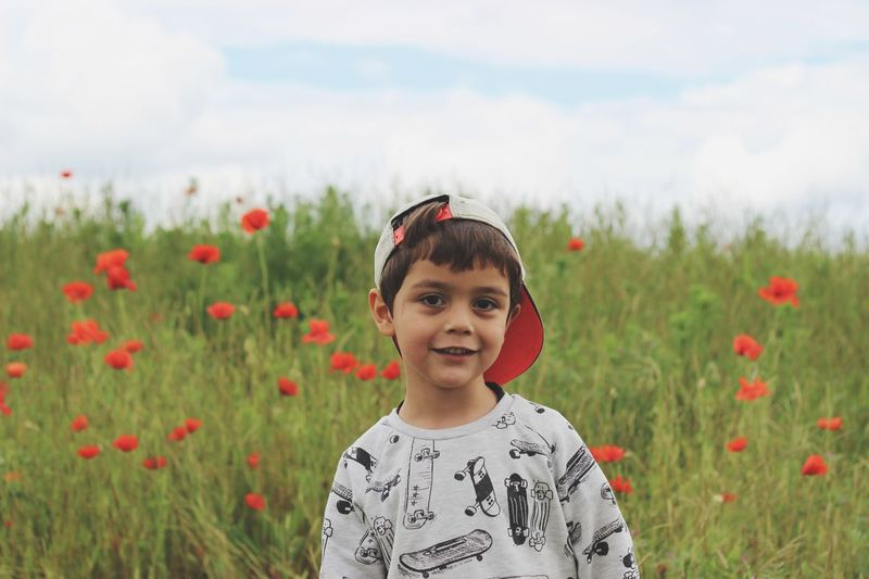 Portrait of boy standing on field against sky