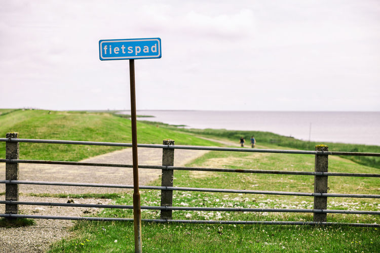Road sign by sea against sky