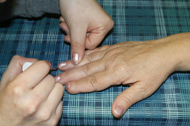 Cropped image of hands applying nail polish
