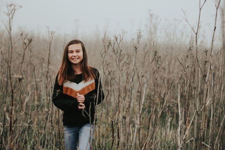 Portrait of smiling girl standing on grassy field against sky