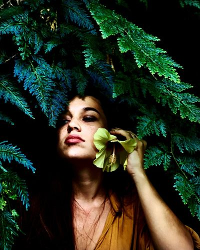 Portrait of young woman looking away against trees