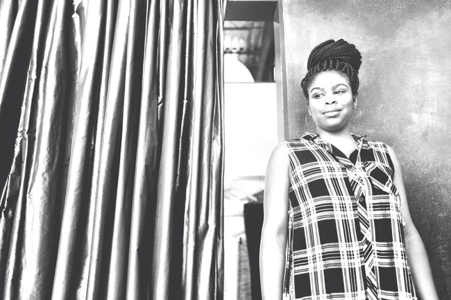 Curtain Young Adult Indoors  Fashion Window One Person Standing Smiling Portrait Day Young Women People Diversity EyeEmNewHere African American Beauty EyeEm Diversity Black People Black & White Plaid Shirt  Beautiful Woman Braids Welcome To Black The Portraitist - 2017 EyeEm Awards
