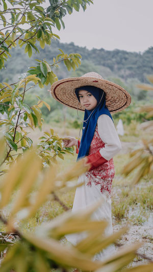 Little girl wearing hijab and a sun hat doing farming. Brunei INDONESIA Nature Day Farming Full Length Girl Hat Hijab Lifestyles Looking At Camera Mala Malaysia Nature One Person Outdoors Portrait Real People Smiling Standing Sun Hat Traditional Clothing Tree Women Young Adult