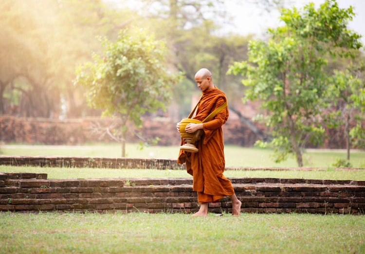 Full length of monk walking on grassy field at park