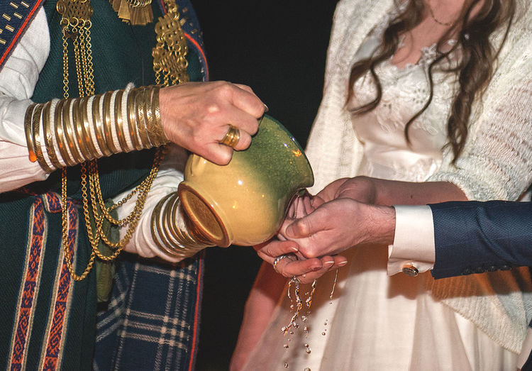 Midsection of man pouring water on bride and groom hands during wedding