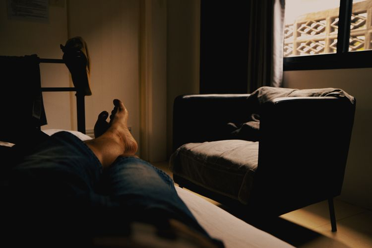 Low section of man resting on bed at home