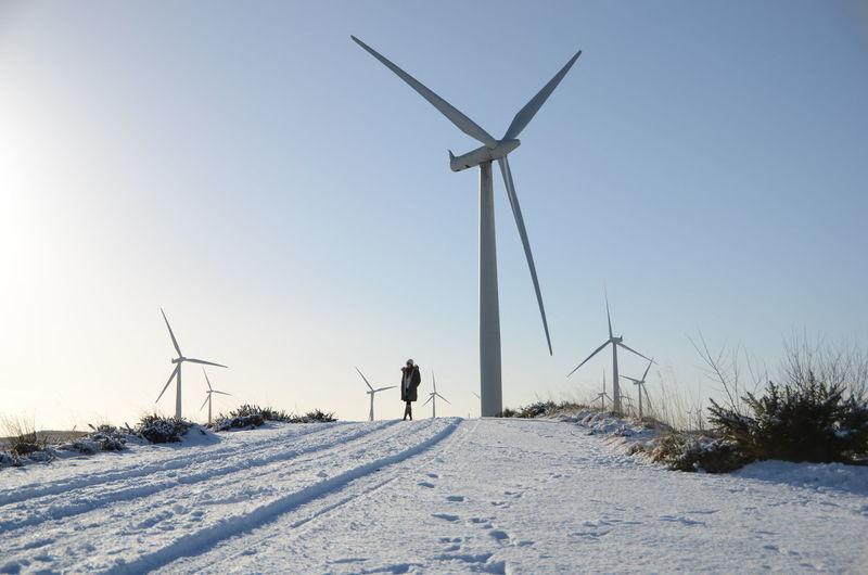 Wind turbines on snowed landscape against clear sky