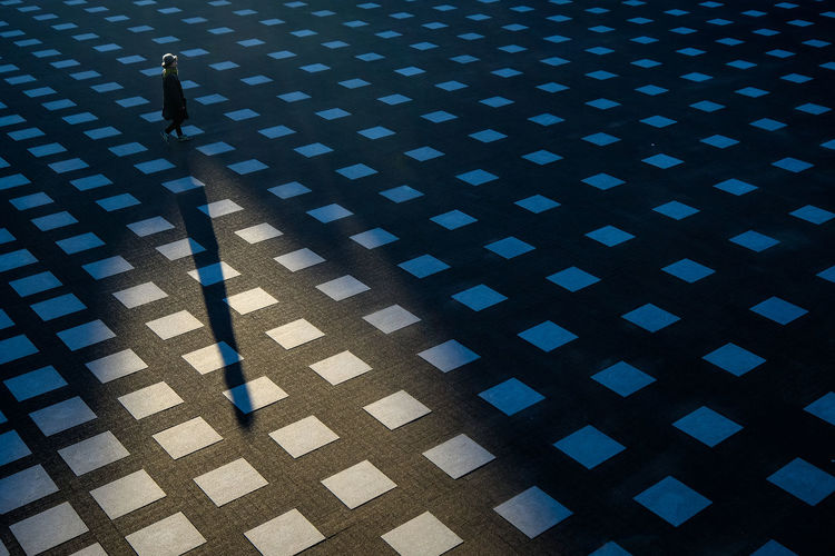 High angle view of man walking on tiled floor