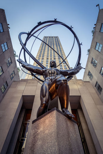 Atlas is a bronze statue in front of Rockefeller Center within the International Building's courtyard in midtown Manhattan, New York City, across Fifth Avenue from St. Patrick's Cathedral. The sculpture depicts the Ancient Greek Titan Atlas holding the heavens. 5th Avenue Atlas Bronze Greek NY NYC New York New York City Rockefeller Center Statue USA Architecture Building Exterior City Day Heavens Low Angle View No People Outdoors Sculpture Statue Titan Tourism Urban Urban Skyline