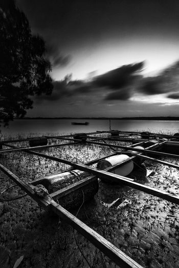 Floating structure of floating fish cage Fish Cage Long Exposure Muddy Seascape Landscape Offshore Fish Fish Floating Cage Water Tranquility Sky Tranquil Scene Nautical Vessel Scenics Transportation Beauty In Nature Nature Day Horizon Over Water Outdoors Cloud - Sky Tree Moored No People Sea