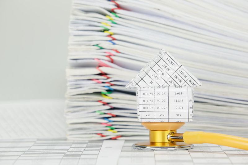 House on yellow and gold stethoscope on finance account have blur pile paperwork of report with colorful paperclip as background. Business Care Doctor  Gold Home Planning Stack Therapy Work Account Document Health House Invest Medical Paper Paperwork Pile Report Stethoscope  Success Treatment White Workload Yellow
