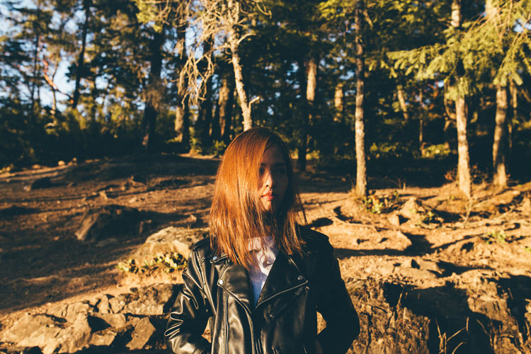 Young Woman Wearing Leather Jacket Against Trees During Sunset