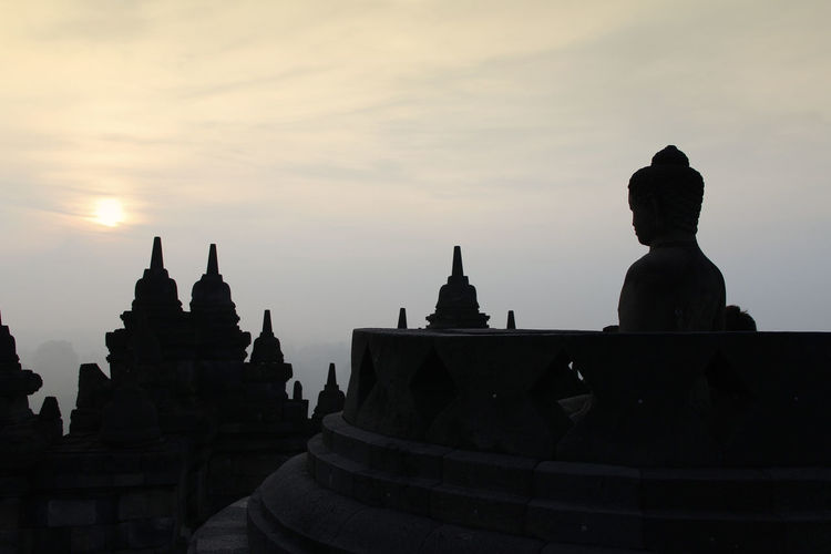 Silhouette Borobudur Temple with the Buddha statue during sunrise, Yogyakarta, Indonesia Borobudur Temple Yogyakarta Ancient Civilization Architecture Belief Buddhism Building Built Structure Dawn History Nature No People Place Of Worship Religion Silhouette Sky Spirituality Sunrise The Past Tourism Travel Destinations