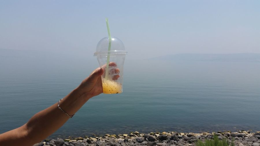 Cropped hand holding slush against lake tiberius during foggy weather