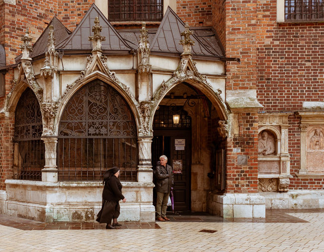 Architecture Built Structure Building Exterior Arch Adult Full Length Building Women Two People Men Real People People Brick Wall Standing Day Lifestyles Wall Place Of Worship Religion Brick Couple - Relationship Outdoors Krakow Kraków, Poland Cracow Cracovia  Priest Noon EyeEm Best Shots EyeEmNewHere EyeEm Selects EyeEm The Street Photographer - 2019 EyeEm Awards