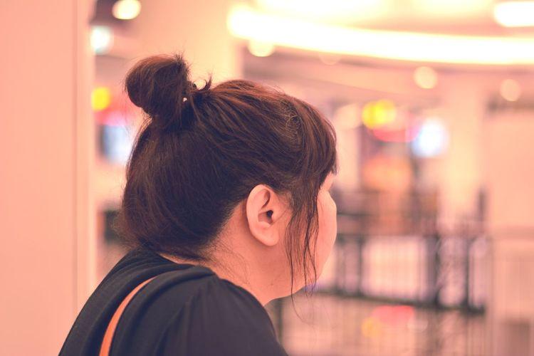 Close-up of woman with bun looking away