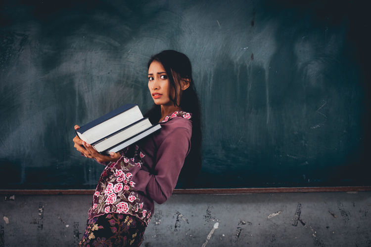 Portrait Of Young Woman Carrying Books While Walking Against Blackboard In Classroom