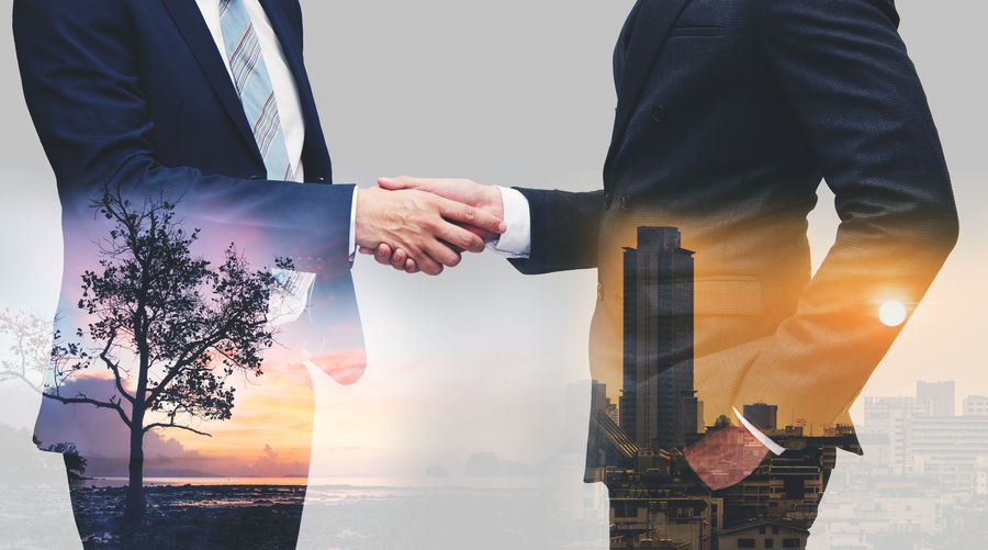 Multiple exposure of business people doing handshake with view of cityscape and seascape