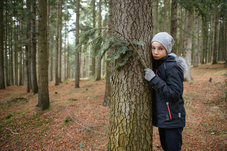 Contemplating girl leaning on a tree trunk and holding a fir branch Tree Land Forest One Person Tree Trunk Trunk Plant Standing Clothing Nature Warm Clothing WoodLand Three Quarter Length Lifestyles Day Winter Outdoors Contemplation Scarf Girl Child Fir Tree