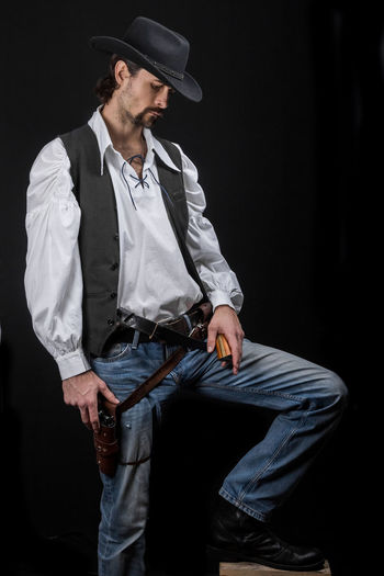 Handsome young man. This is an American cowboy. A vow to a white shirt, brown waistcoat and blue jeans. Black shoes on the feet. Carries a shtyapa, on a belt two pistols. The hair is of medium length; on the face is a beard and mustache. Authentic photo. Culture of America. Cowboy Wild West America American Gun National Authentic Moments Lifestyles Lifestyle One Person Candid Authentic Hat Three Quarter Length Clothing Young Men Young Adult Black Background Men Adult Mid Adult Casual Clothing Weapon Handgun Jeans