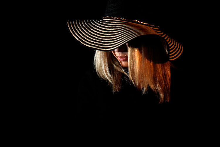 Woman wearing hat against black background