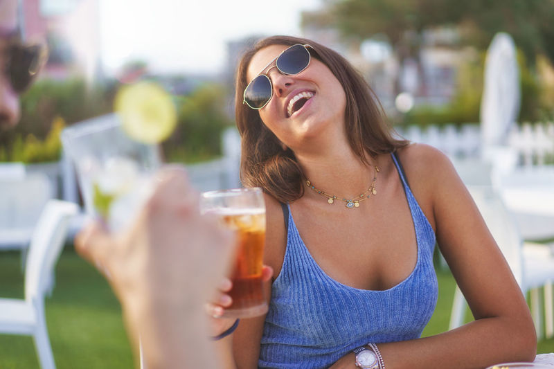 Couple having fun drinking fresh cocktails and beers outdoors wearing sunglasses