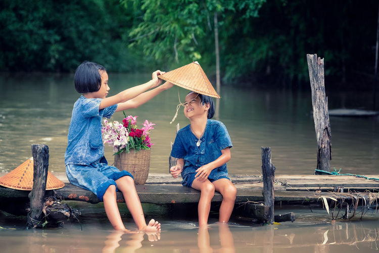 water, background, sitting, bridge, people, wooden, nature, young, lifestyle, children Water Sitting Lake Two People Nature Leisure Activity Real People Togetherness Women Full Length Childhood Hat Family Men Casual Clothing Lifestyles Bonding Child Outdoors Positive Emotion Sister