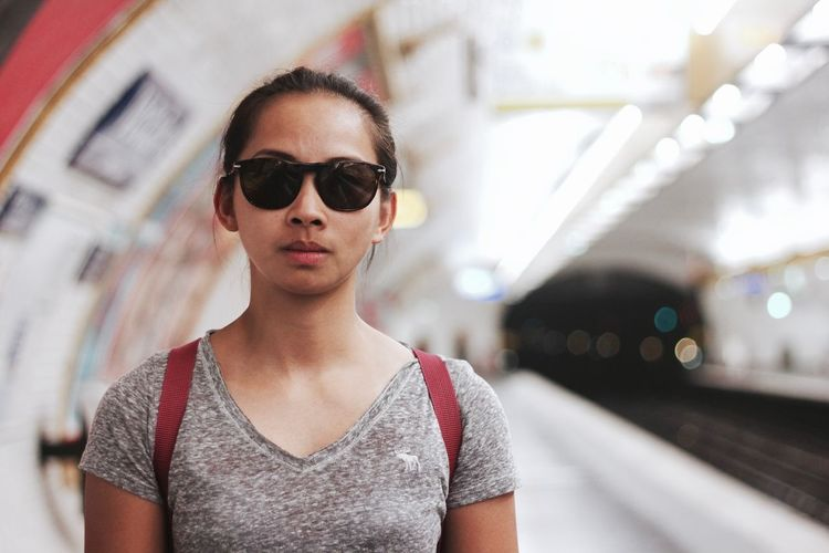 Portrait of young woman wearing sunglasses at subway station